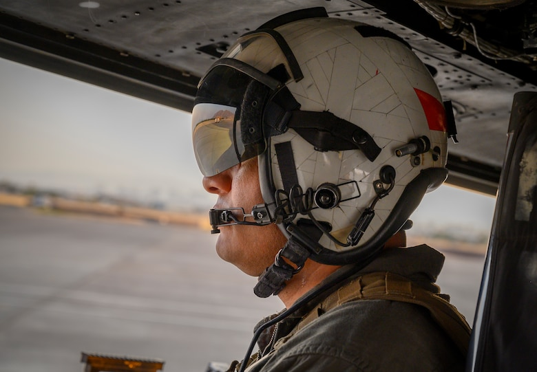 Marine looks out of helicopter on flight line.