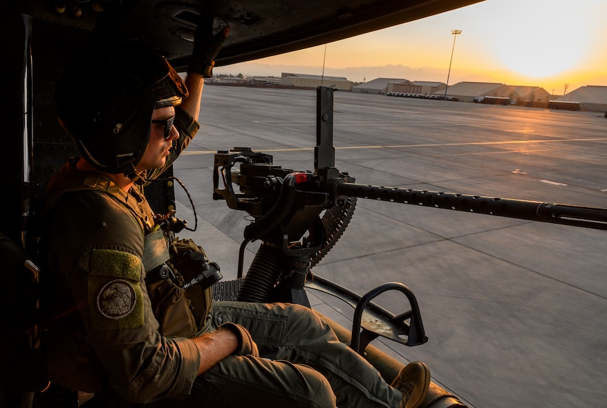 Marine sits in helicopter on flight line.