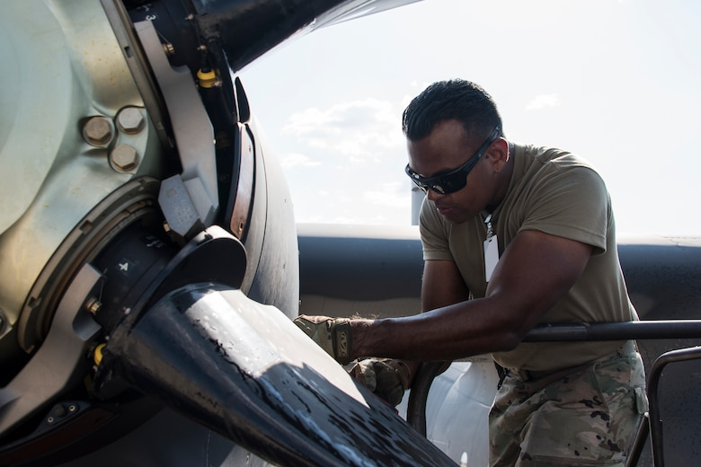 A photo of an Airman performing maintenance on an HC-130J