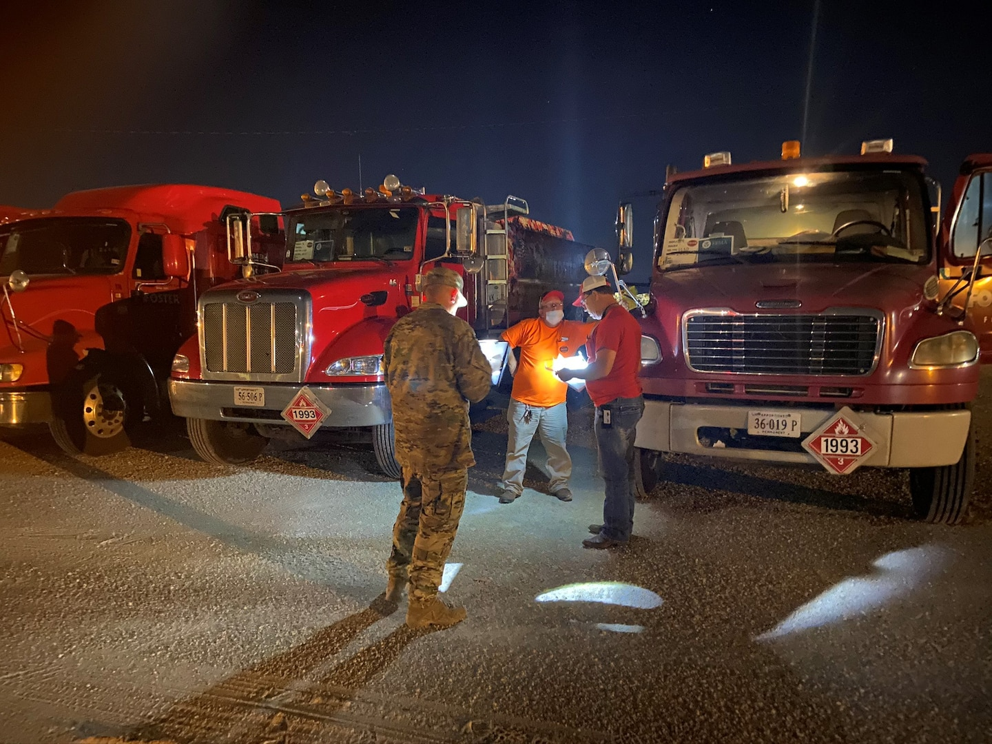 A man in uniform talks with fuel truck drivers by their trucks