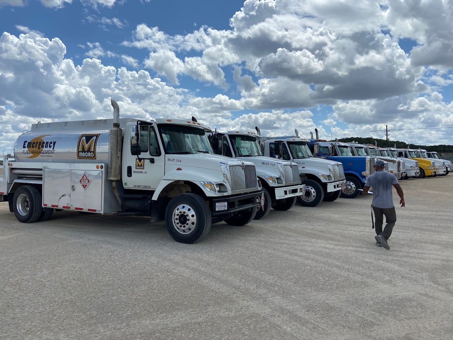 a line of fuel trucks parked with a man walking in front