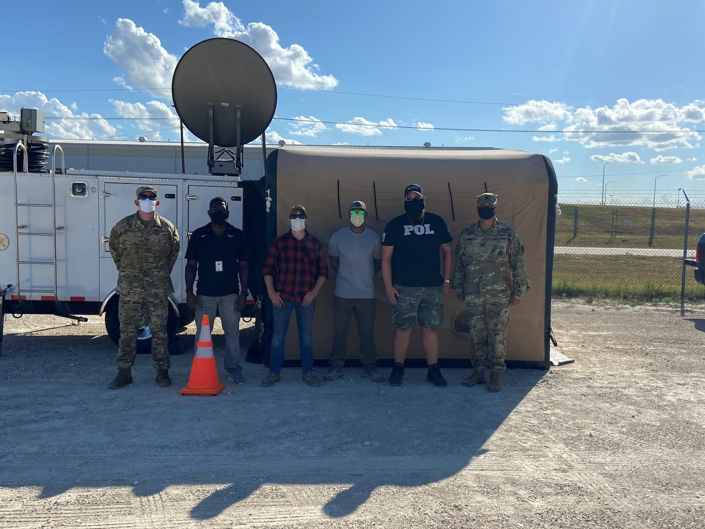 six people stand in front of an emergency communication trailer