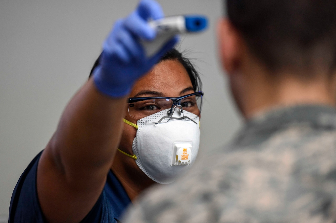 A woman wearing a face mask hold a thermometer up to the forehead of a aims a military service member.