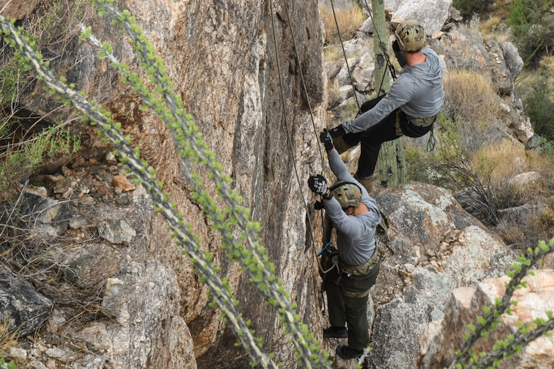 A photo of an Airman rappelling down a rock