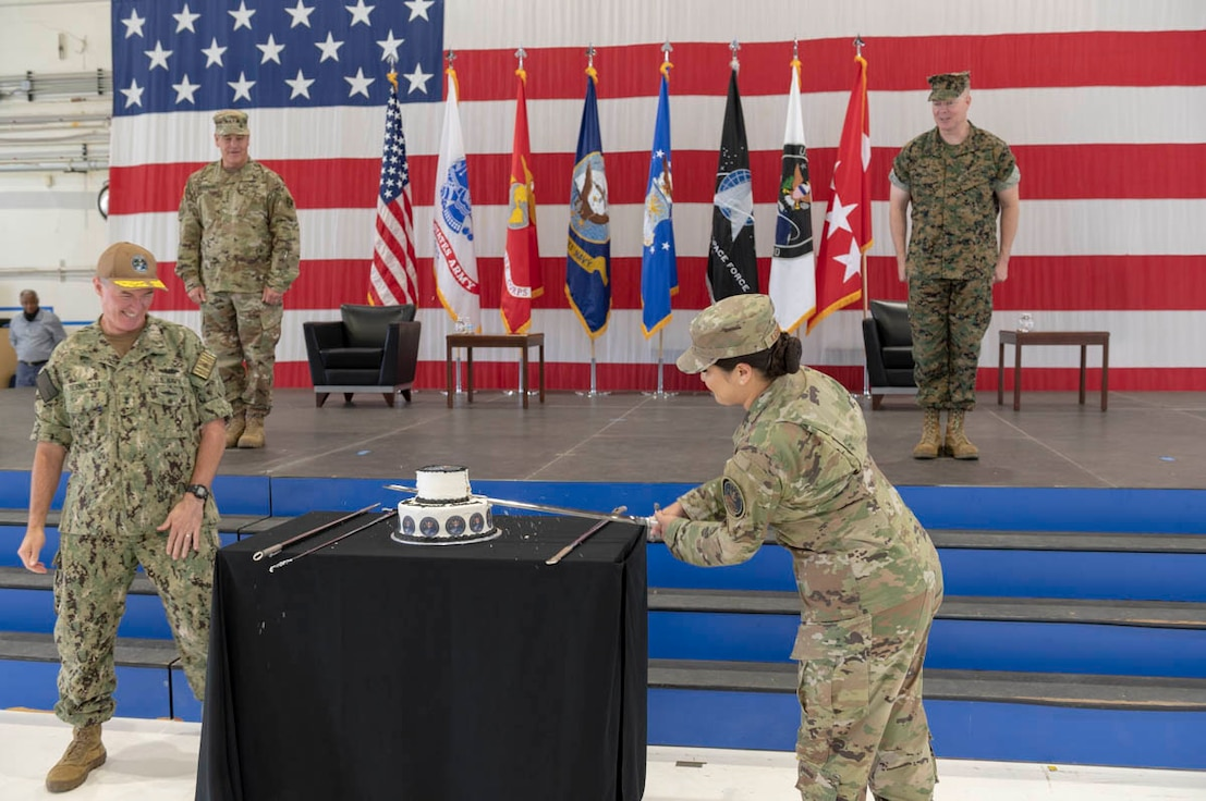 """U.S. Air Force Staff Sgt. Kiara Kashner, right, and U.S. Navy Rear Adm. Michael Bernacchi, representing U.S. Space Command's longest-serving and junior-serving members, respectively, cut a cake in honor of the combatant command's first birthday Aug. 28, 2020, at Peterson Air Force Base, Colorado. Kashner serves as executive assistant to the commandant and Bernacchi is Strategy, Plans and Policy director. USSPACECOM was officially established Aug. 29, 2019, during a ceremony in the White House Rose Garden with President Donald Trump; Dr. Mark T. Esper. Secretary of Defense; and Gen. John W. """"Jay"""" Raymond, former USSPACECOM commander and current U.S. Space Force Chief of Space Operations; and Chief Master Sgt. Roger Towberman, former USSPACECOM command senior enlisted leader and current USSF CSEL."""