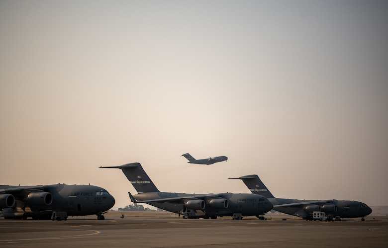 A C-17 takes off behind a row of other C-17s.