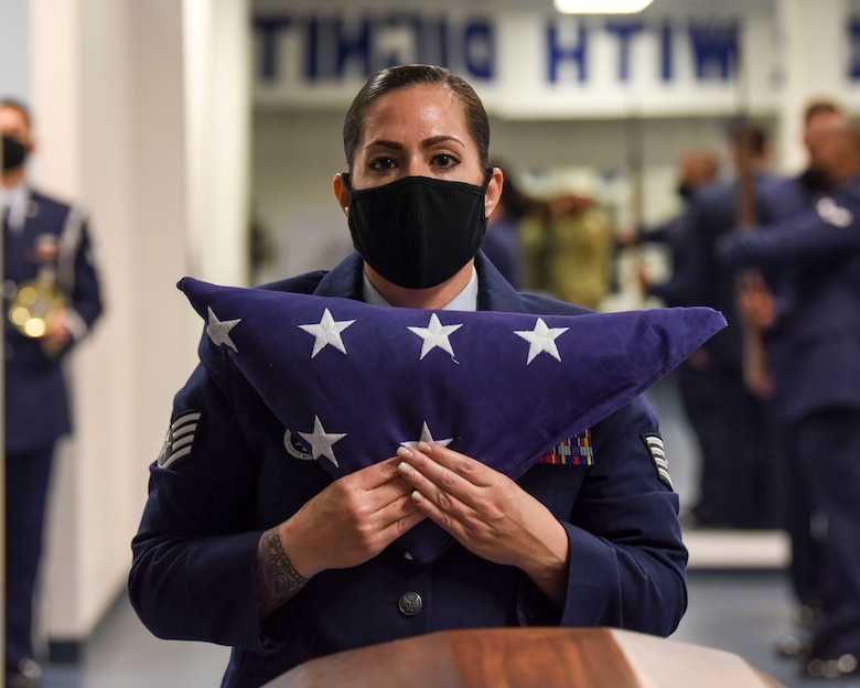 """U.S. Air Force Staff Sgt. Kara Tierney, ceremonial guardsman with the Joint Base Elmendorf-Richardson Honor Guard, presents a United States flag during a 6-man funeral sequence during an Honor Guard graduation ceremony at Joint Base Elmendorf-Richardson, Alaska, Aug. 26, 2020. The primary mission of the base Honor Guard program is to employ, equip and train Air Force members to provide professional military funeral honors for active duty members, retirees and veterans. In January of 2000, public law was implemented, providing all veterans the right to a funeral ceremony that includes, at minimum, the folding of a U.S. flag, presentation of the flag to the veteran's family and the playing of """"Taps."""" (U.S. Air Force photo by Senior Airman Crystal A. Jenkins)"""