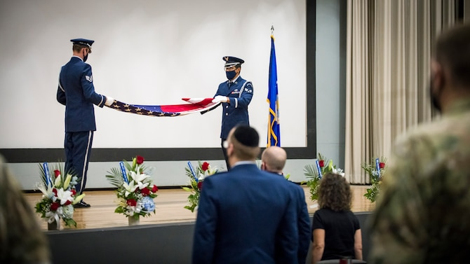 The Blue Eagles Honor Guard fold a U.S. flag in during a memorial ceremony at Edwards Air Force Base, California. The memorial service was in honor of the 13 Team Edwards members who have passed away this year. (Air Force photo by Giancarlo Casem)