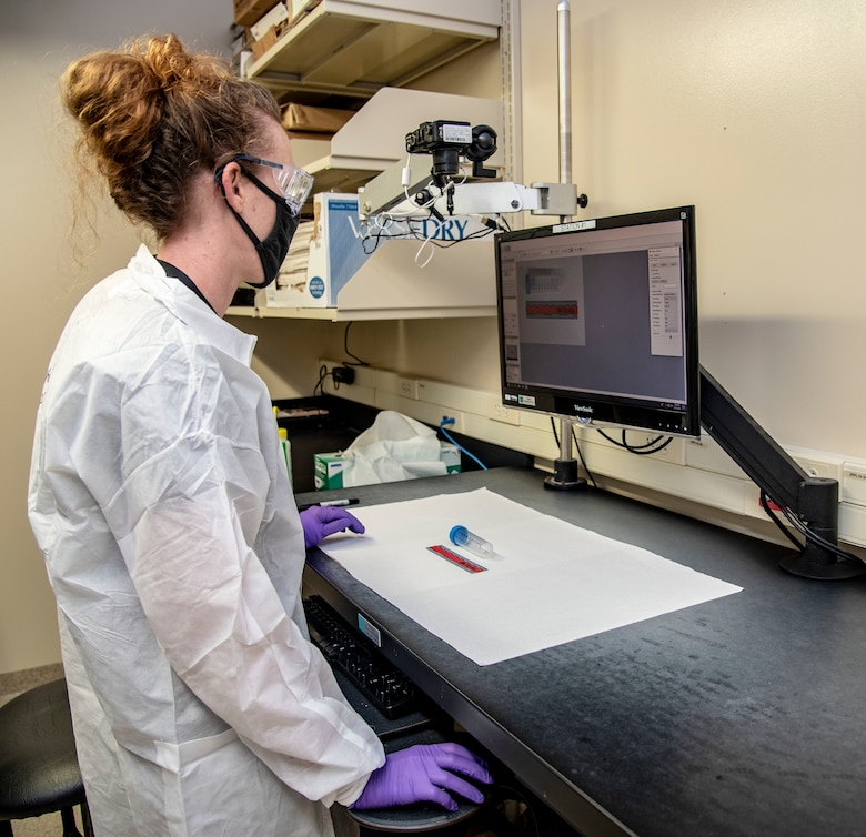 Rachel Johnson, Armed Forces Medical Examiner System Department of Defense DNA Operations evidence custodian, looks at a computer screen, with a sample test tube sitting in front of her on the desk.
