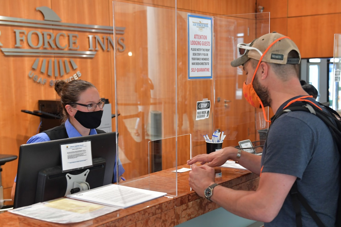 A hotel worker helping a customer at the front desk.