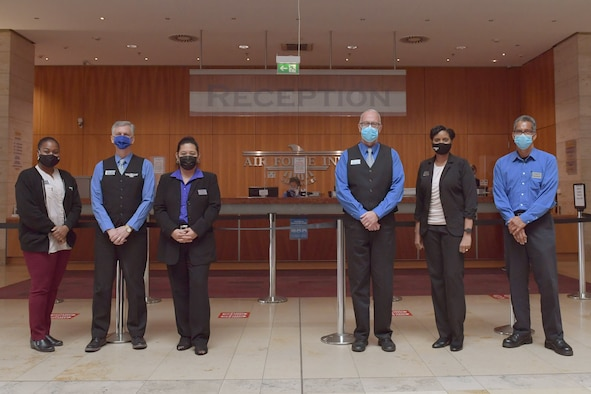 Hotel workers standing in a lobby.