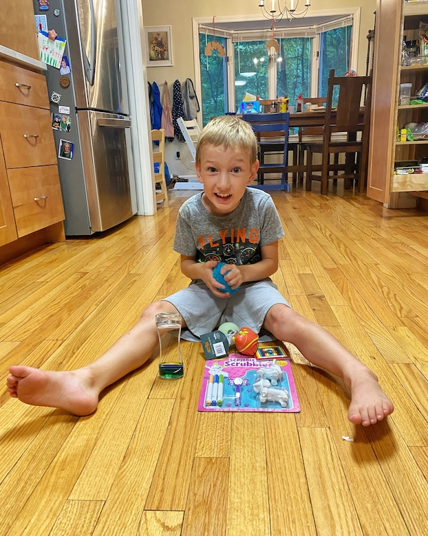 Abraham Lemery, a U.S. Air Force family member, holds toys from a sensory box in his home outside Amherst, Mass., earlier this month. The Hanscom Exceptional Family Member Program sent the boxes to enrolled families to supplement therapy for children on the Autism Spectrum or with sensory processing needs. (Photo courtesy of Lt. Col. Dave Lemery)