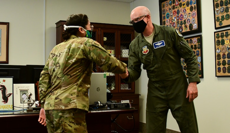 A photo of an officer receiving a coin from a general.
