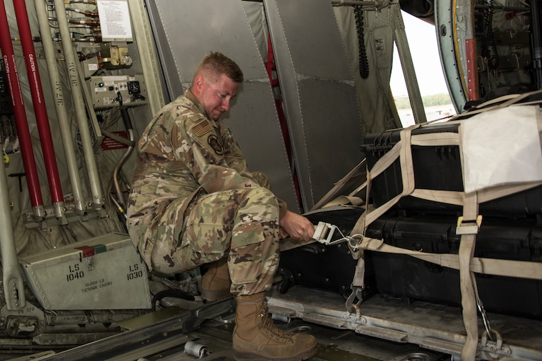 A photo of Airmen strapping down cargo
