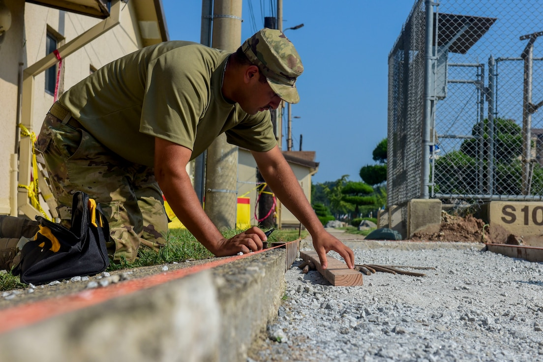 .Staff Sgt. Jimmy Noriega, 8th Civil Engineer Squadron heavy equipment and pavement craftsman, measures the sidewalk for construction at Kunsan Air Base, Republic of Korea, Aug. 23, 2020. This sidewalk construction is part of the final stages of a larger road work project located in front of the Community Bank. (U.S. Air Force photo by Senior Airman Jessica Blair)