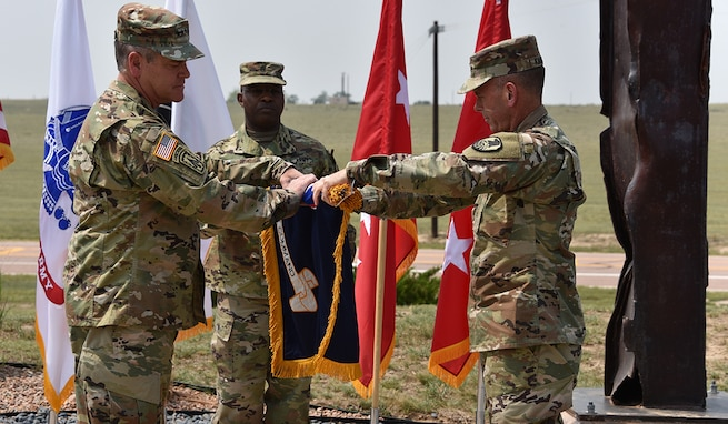 Gen. James H. Dickinson, U.S. Space Command commander, left, and Lt. Gen. Daniel L. Karbler, U.S. Army Space and Missile Defense Command commanding general, unfurl SMDC's colors to officially recognize the command as the Army Service Component Command to USSPACECOM during a ceremony at Schriever Air Force Base, Colorado, Aug. 21. (U.S. Army photo by Dottie K. White)