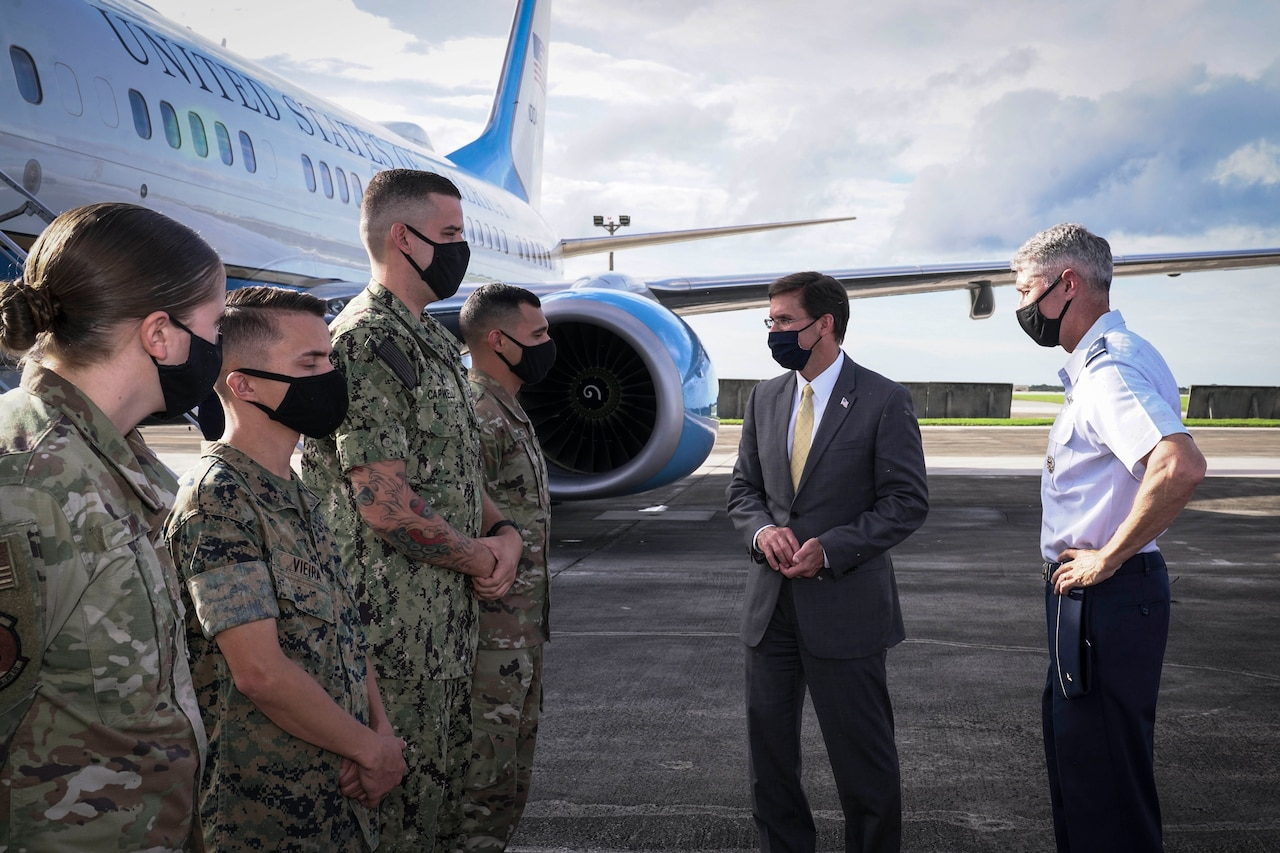 Man in civilian business suit greets military personnel on the tarmac. All are wearing masks. Official airplane is in the background.