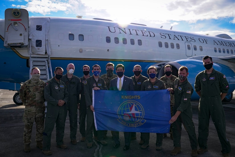 A man in business attire stands with men in military uniforms. All are wearing masks. An official airplane is in the background.