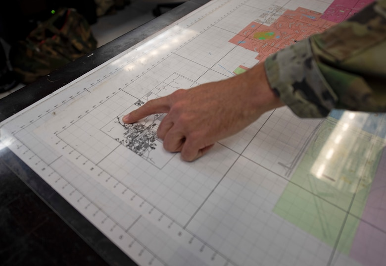 U.S. Air Force Staff Sgt. Michael Itami, 60th Security Forces Squadron emergency communications center controller, points at a map of the base Aug. 24, 2020, at Travis Air Force Base, California. The SFS was notified Aug. 19 to evacuate more than 8,000 base personnel due to the wildfires that have burned more than 1.5 million acres in the surrounding area. (U.S. Air Force photo by Senior Airman Jonathon Carnell)
