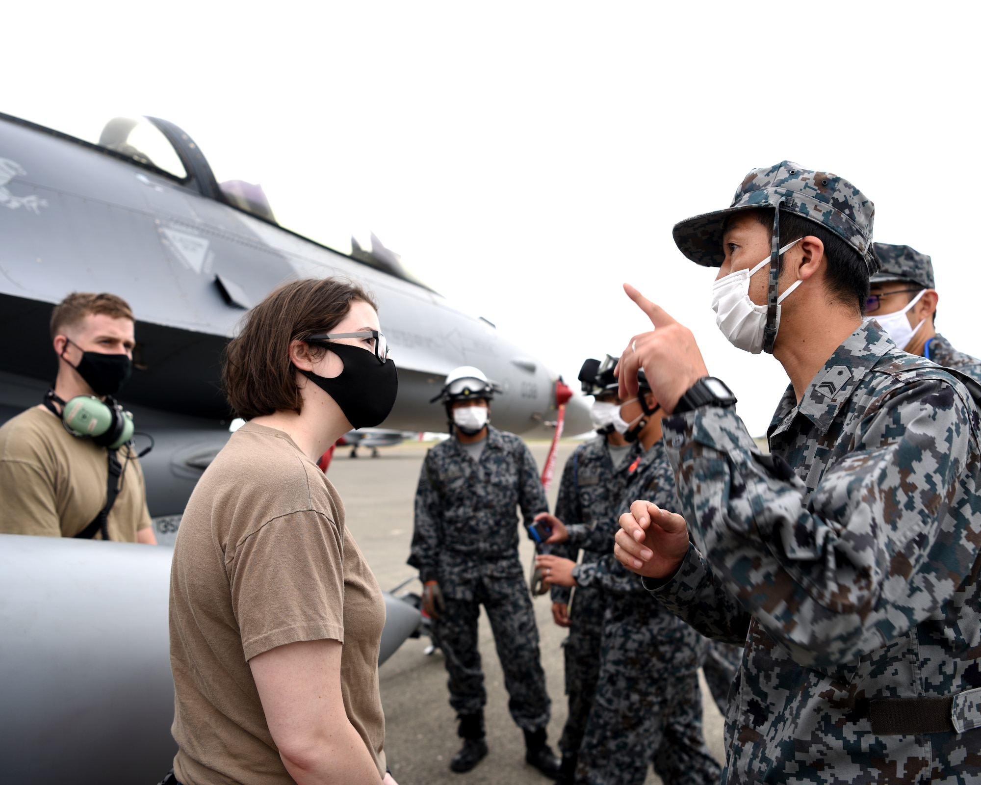 U.S. Air Force Tech. Sgt. Bailey Delaney, 13th Aircraft Maintenance Squadron debrief NCO-in charge, explains F-16 operations to Koku-Jieitai personnel during Aviation Training Relocation at Chitose Air Base, Japan Aug. 25, 2020.
