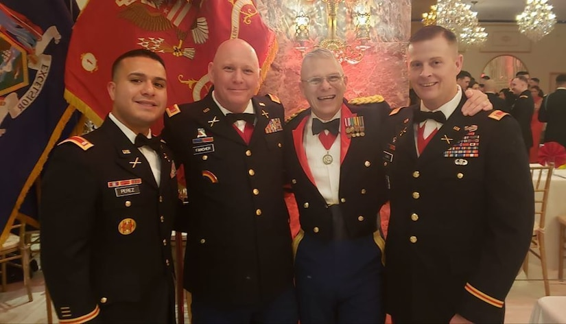 Chief Warrant Officer 4 Thomas Fancher ( second fron the left) stands with Chief Warrant Officer 2 Carlos Perez, Chief Warrant Officer 3 Shawn Stanford and Chief Warrant Officer 3 Ben Lewis ( far right) at the 1-258th Field Artillery Battalion dining out St. Barbara's Ball December 7, 2019.