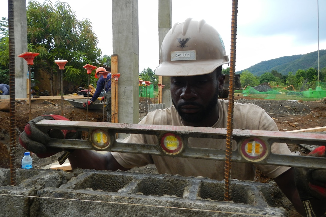 At a construction site, a man wearing a hard hat places a level on top of a concrete block.