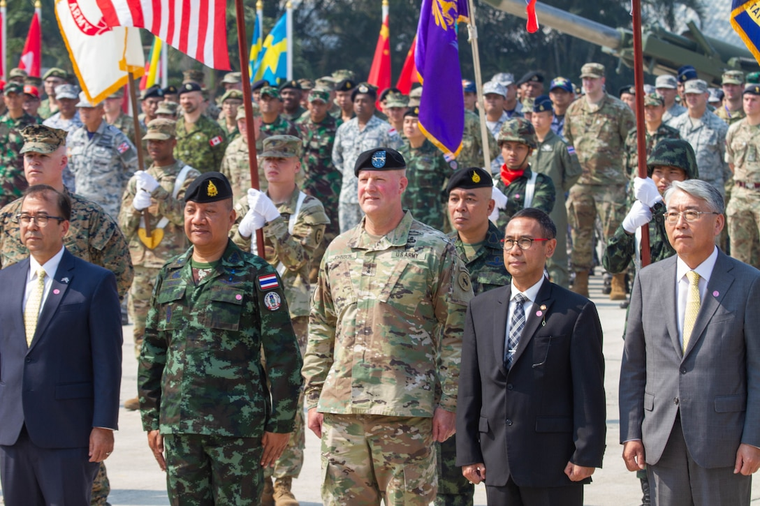Officers, soldiers and civilian leaders from many different countries stand in formation.
