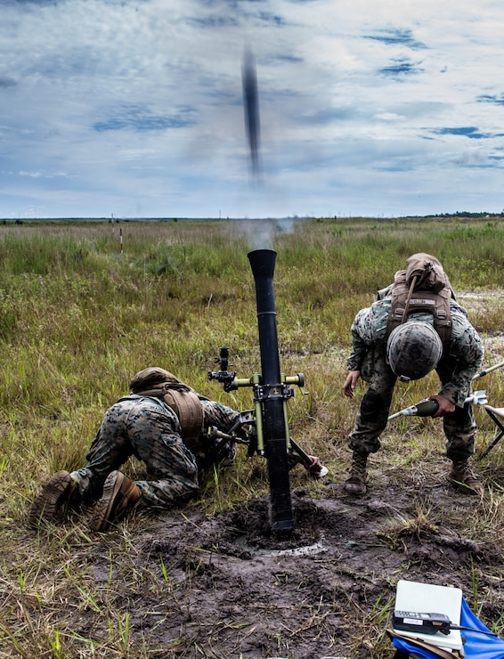 U.S. Marine Corps Lance Cpl. Dewayne Graham, left, and Cpl. Guilherme Neto, both mortarmen with 2d Battalion, 6th Marine Regiment (V26), 2d Marine Division fire 81 mm mortars during live-fire training at Camp Lejeune, Aug. 25, 2020. The Marines with V26 are training to expand their knowledge and abilities with mortars..