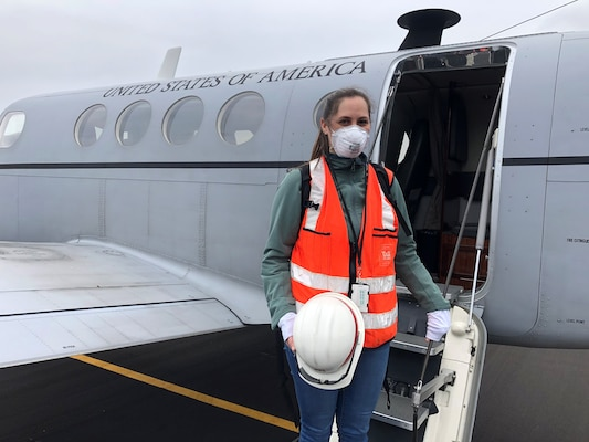 masked woman stands on stairs of airplane