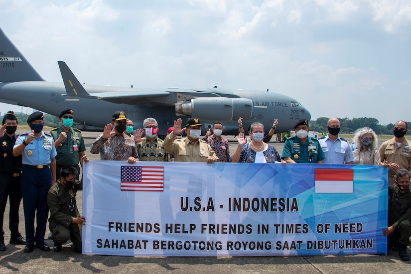 """With a large plane in the background, a group of more than 20 people pose for a photo while holding a banner with the words """"USA-Indonesia Friends Help Friends in Time of Need."""