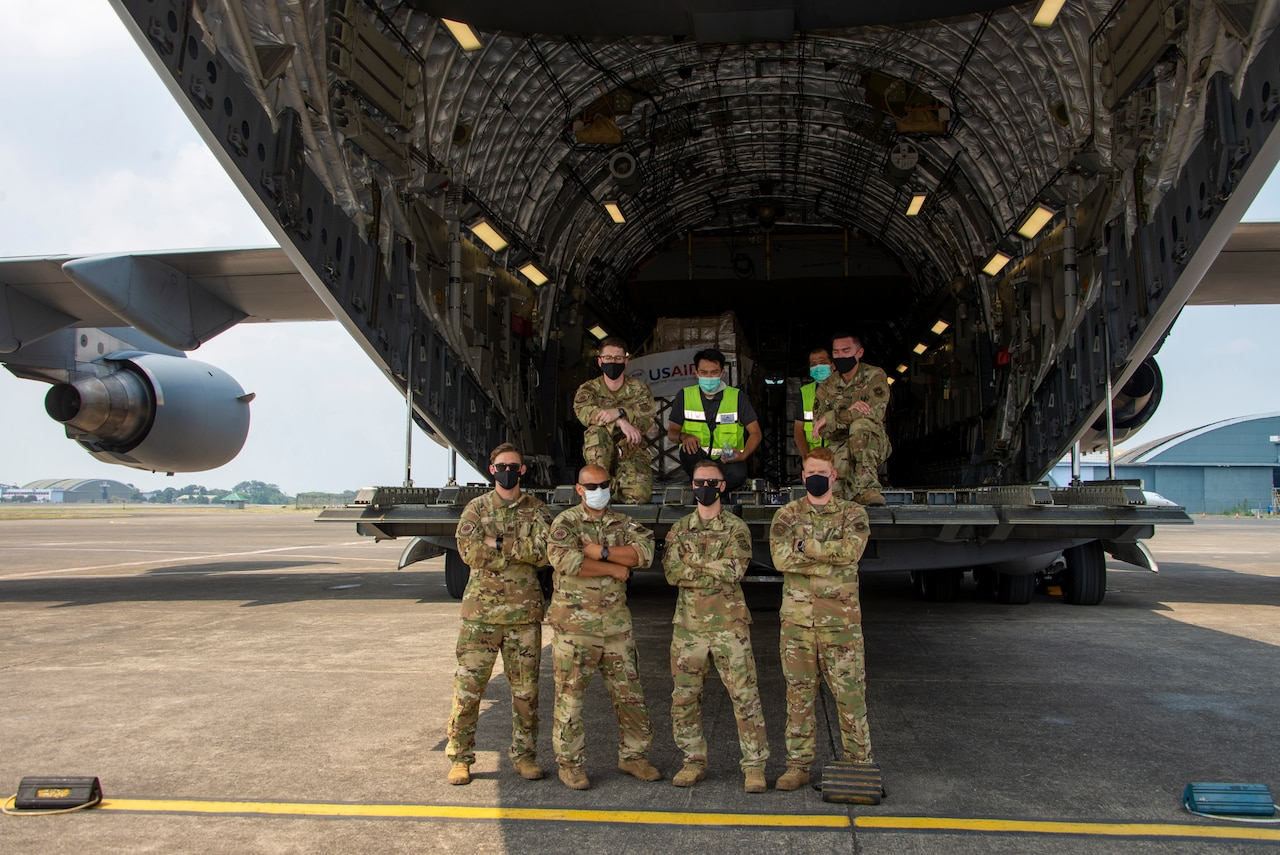 Eight service members wearing face masks stand at the back of a cargo plane and pose for a photograph.