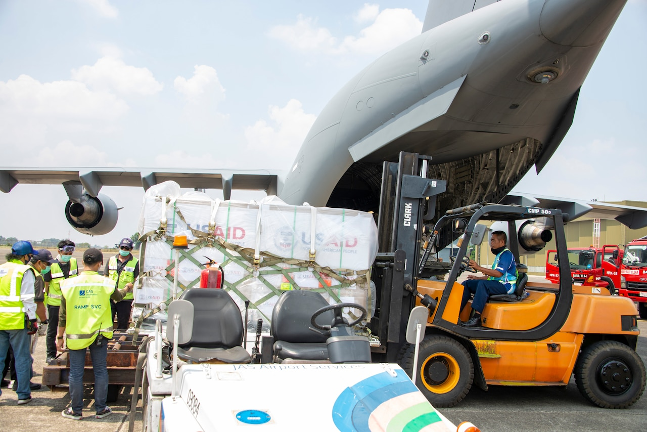 A man driving a forklift moves boxes secured to pallets from an airplane.
