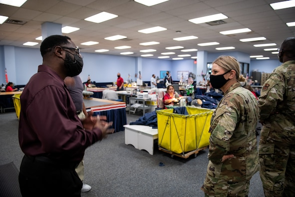 Man wearing a mask speaking to a woman in military uniform. People sewing clothing in the background.