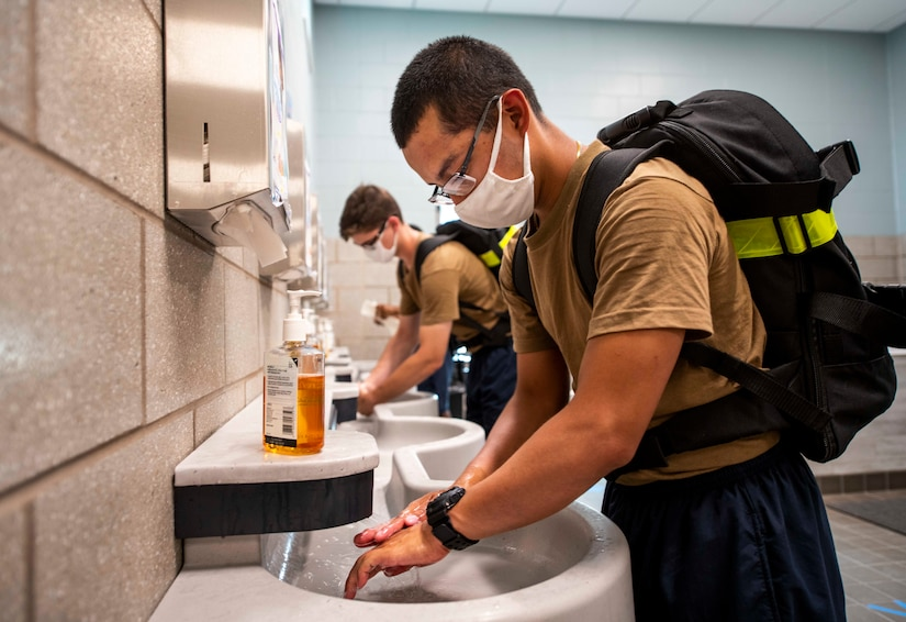 Navy recruits wearing backpacks and face masks wash their hands in bathroom sinks.