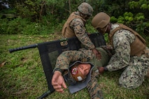 U.S. Naval Corpsman with Marine Light Attack Helicopter Squadron 369 load a simulated casualty onto a litter during Casualty Evacuation (CASEVAC) training on Marine Corps Air Station Futenma, Okinawa, Japan, March 12, 2020. The CASEVAC training was conducted by HMLA-369 and supported by Marine Air Group 36, Naval Hospital Okinawa in addition to the Air Force 33rd Rescue Squadron to enhance readiness and proficiency in response to emergencies while deployed in a field environment. (U.S. Marine Corps photo by Lance Cpl. Ethan M. LeBlanc)