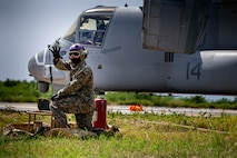 U.S. Marine Corps Cpl. Eliecer Echavarria, a point operator with Marine Wing Support Squadron (MWSS) 172, provides hand signals to indicate the number of gallons going into the MV-22 Osprey in support of assault support aircraft from 1st Marine Aircraft Wing during Operation Lightning Strike, Aug. 6, 2020, at Ie Shima Training Facility, Okinawa, Japan. The purpose of the training was to prepare Prospective Weapons and Tactics Instructor (PWTI) students for what to expect when they attend future WTI courses. MWSS-172's role was to provide the Forward Arming and Refueling Point to expand the combat radius and allow aviation ground support closer to the objective. (U.S. Marine Corps photo by Lance Cpl.  Karis Mattingly)