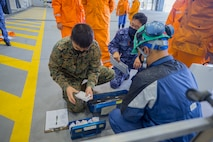 U.S. Marine Corps Sgt. Meanong Lor, an aircraft electrical systems technician with Marine Aerial Refueler Transport Squadron 152 and Japan Maritime Self-Defense Force personnel with Maintenance and Supply Squadron 31 inspect tools during Exercise Keen Sword 2021 at Marine Corps Air Station Iwakuni, Japan, Nov. 2, 2020. Keen Sword is a series of joint/bilateral training exercises designed to increase combat readiness and interoperability of Japan Self-Defense Force and U.S. forces. (U.S. Marine Corps photo by Lance Cpl. Tyler Harmon)