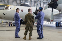 A U.S. Marine with Marine Aerial Refueler Transport Squadron 152 speaks with Japan Maritime Self-Defense Force personnel with Maintenance and Supply Squadron 31 during Exercise Keen Sword 2021 at Marine Corps Air Station Iwakuni, Japan, Nov. 2, 2020. Keen Sword is a series of joint/bilateral training exercises designed to increase combat readiness and interoperability of Japan Self-Defense Force and U.S. forces. (U.S. Marine Corps photo by Lance Cpl. Tyler Harmon)