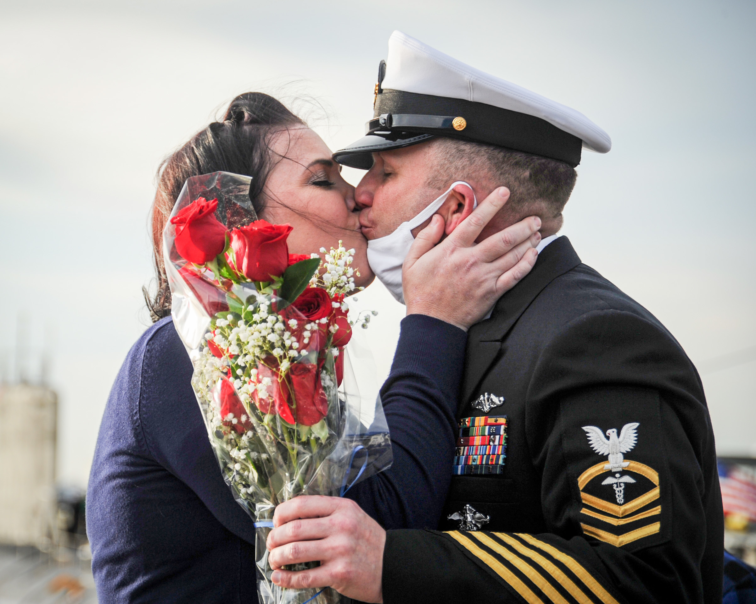 Chief Hospital Corpsman Dennis Sanders, assigned to the Virginia-class fast-attack submarine USS John Warner (SSN 785), kisses his wife, Lauren Sanders, during the boat's homecoming at Naval Station Norfolk, Nov. 25, 202