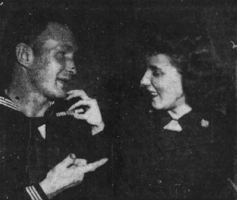 Man and woman in Coast Guard uniforms speak to one another.