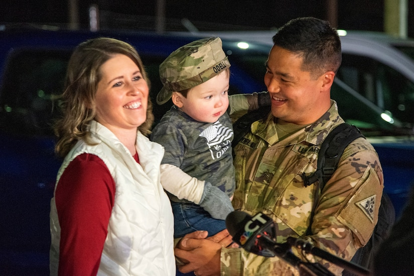 A soldier holds his child while his wife smiles.