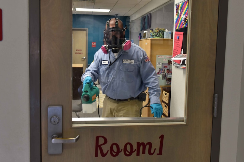 A man disinfects a classroom.