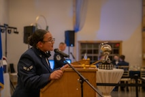 A female Airman leans into a podium to speak to the audience while a male Airman speaks at another podium in the background.