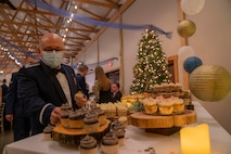 A male Airman is grabbing a cupcake from a cupcake stand with a Christmas tree in the background.