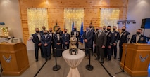 A group of Airmen in dress blues gather around an award and look to the camera for a photo.