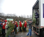 Volunteers pass a tree up to FedEx driver Don Pelletier during the Trees for Troops loadout on Nov. 30, 2020, at Ellms Tree Farm in Ballston Spa, N.Y. More than 20 volunteers from the New York Army and Air National Guard joined with Capital District area veterans to help load about 125 Christmas trees being donated and sent to military bases around the country to support troops and military families this holiday season. This marks the 16th year of military members volunteering their time to assist in loading trees destined for fellow service members and their families around the country and around the world.