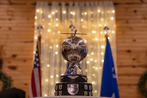 The rotating General Atomics Remotely Piloted Aircraft Squadron of the year trophy which involves a silver metal globe propped up by twisted, metal lightning bolts and topped with a metal RPA sitting in front of the United States flag, the U.S. Air Force flag and white holiday lights.