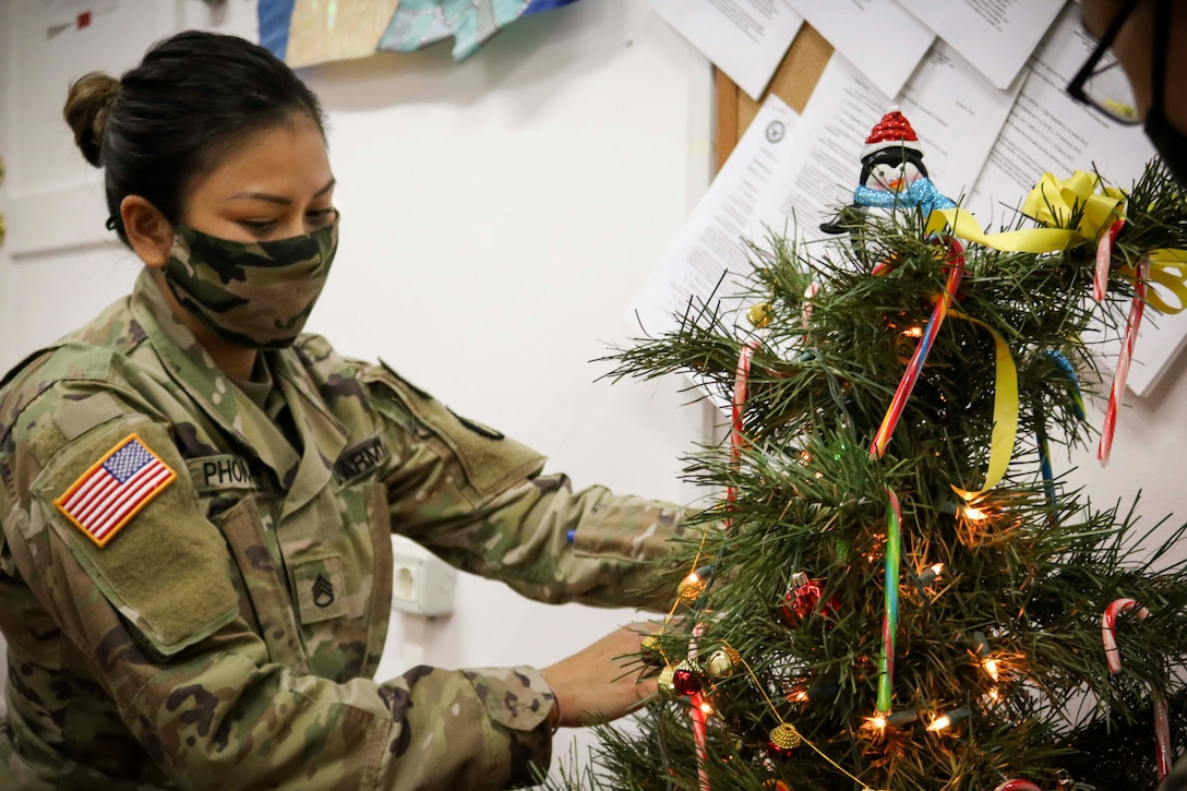 A soldier wearing a mask decorates a Christmas tree.