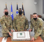 From left, Maj. David Rahl, National Reconnaissance Office Operations Squadron director of operations, Lt. Col. Roland Rainey, NOPS commander and Senior Master Sgt. Joseph Cavallaro, NOPS superintendent, hold a cake recognizing the NOPS's 20th anniversary Oct. 30, 2020, at Schriever Air Force Base, Colorado. The NOPS employs global resources to provide critical connectivity and telemetry, tracking and command data while serving as the single NRO interface to the Air Force Satellite Control Network. (U.S. Space Force courtesy photo)