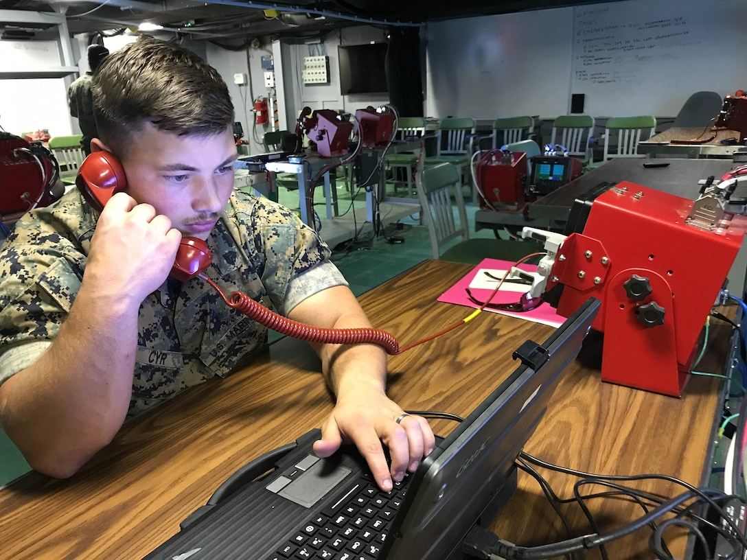 A U.S. Marine performs a functions check on the communications equipment inside the Landing Force Operations Center, Oct. 29.